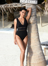 A middle aged woman is wearing a minimalist swimsuit in black colour which she purchased online from sun vixen swimwear