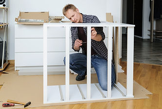 The man is assembling the furniture at