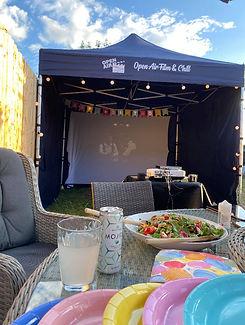 A garden cinema setup inside a marquee
