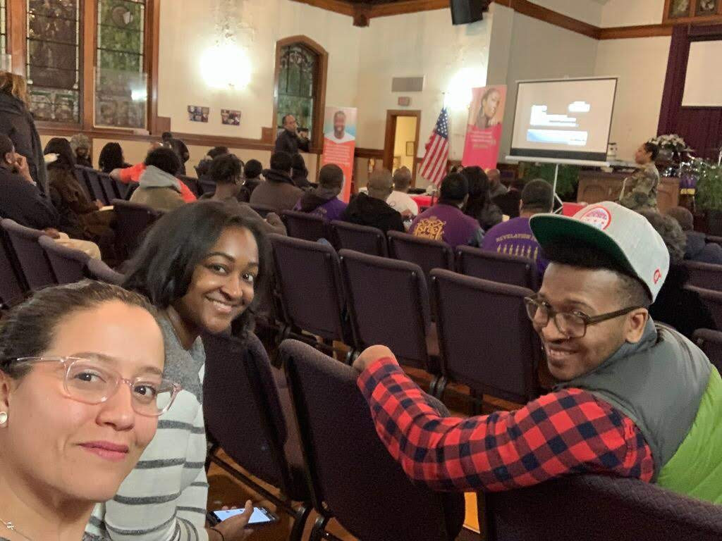 2019 CUE Fellows Paola Aguirre, Tracy Bishop, and Maurice Robinson share the Vote Equity ballot for neighbors to vote on at a meeting of the Residents Association of Greater Englewood (RAGE).