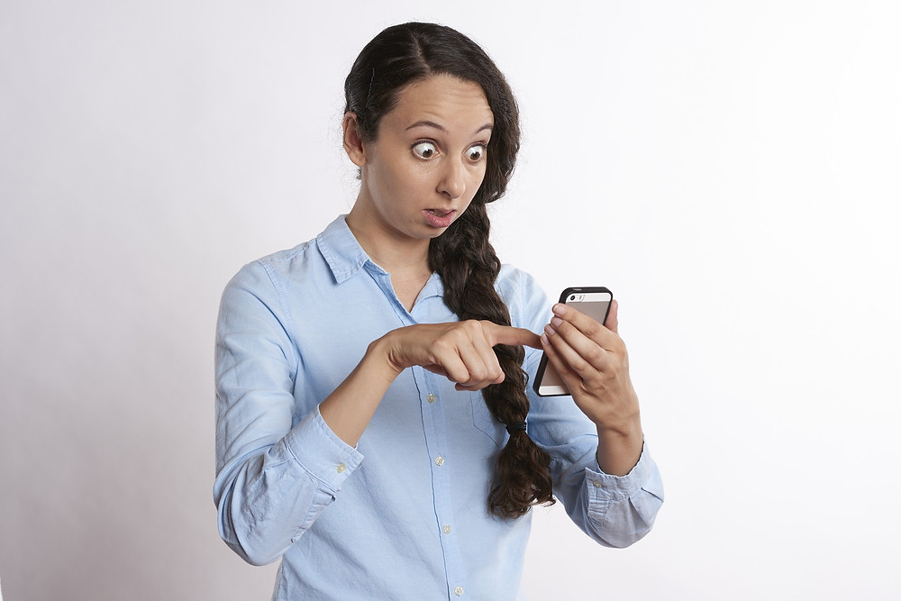 Surprised student holding an mobile phone