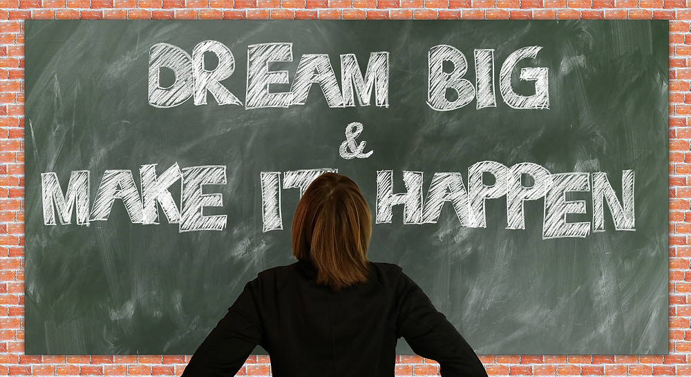 "Teacher looking at chalkboard that says ""Dream Big & Make it Happen"""