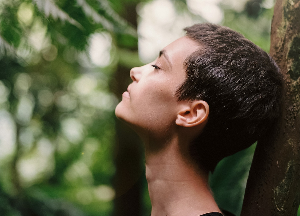 woman leaning against a tree with eyes closed breathing through nose