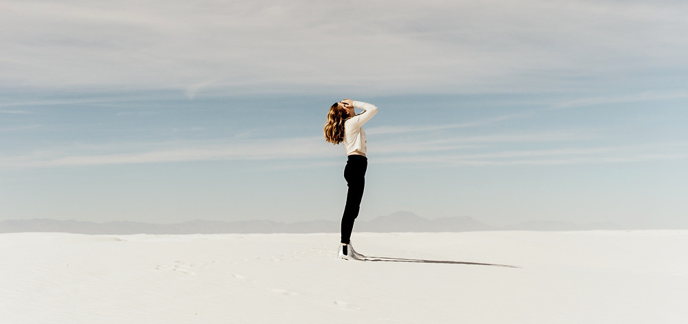 woman in desert face up to sky breathing into her hands