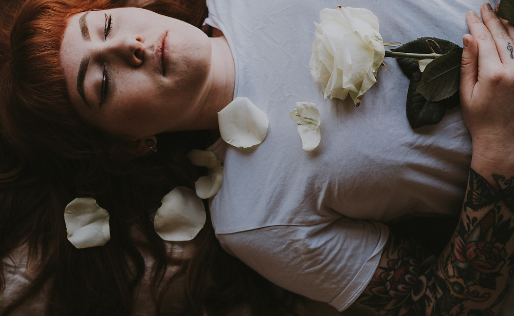 woman practicing breathwork breathing lying down with rose
