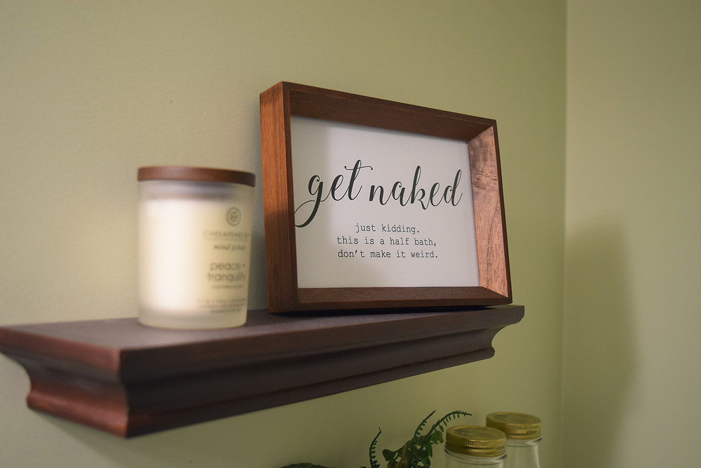 "A close-up of a mahogany shelf with matching photo frame on it, with a print that reads ""get naked just kidding this is a half bath don't make it weird"" and a small white candle beside it"