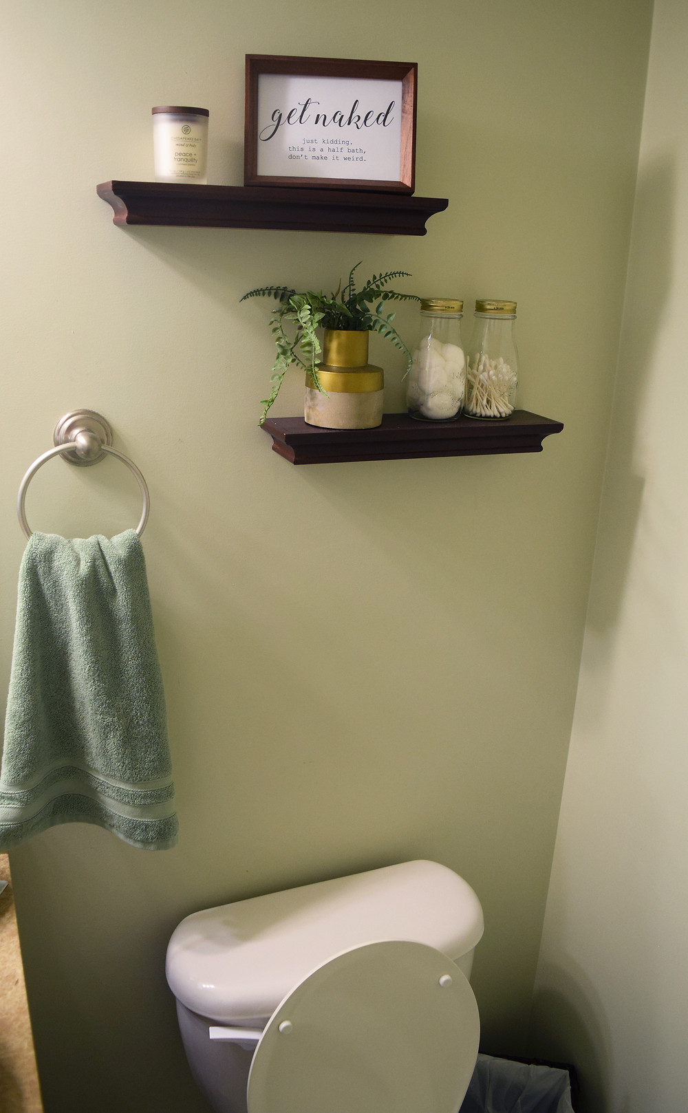 Two floating shelves are above the toilet, with decor on each shelf and a towel ring shown to the left