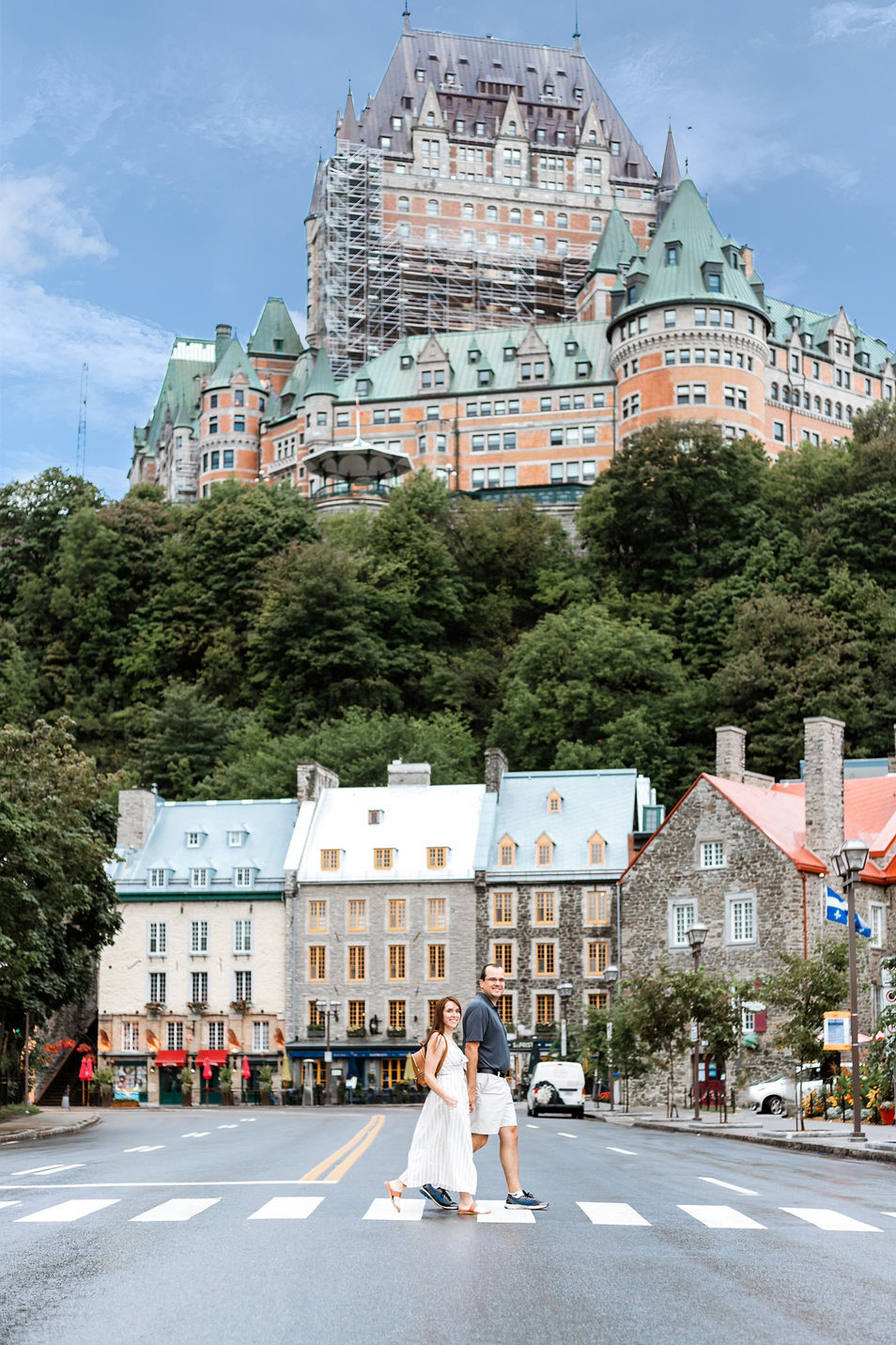 A couple crossing the street in the quartier du petit champlain of old quebec. Chateau Frontenac can be seen in the background.