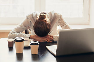 Tired businesswoman sleeping on table in office. Young overworked exhausted girl working f