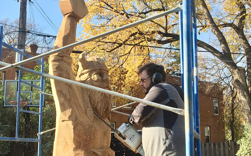 "Chainsaw artist Jason Soderlund uses his chainsaw on the ""Viking Elm,"" on South Fifth Street in Grand Forks. (Adam Kurtz/ Grand Forks Herald)"