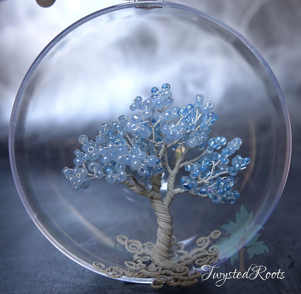 Light blue and ivory coloured bead and wire tree sculpture in an acrylic bauble.