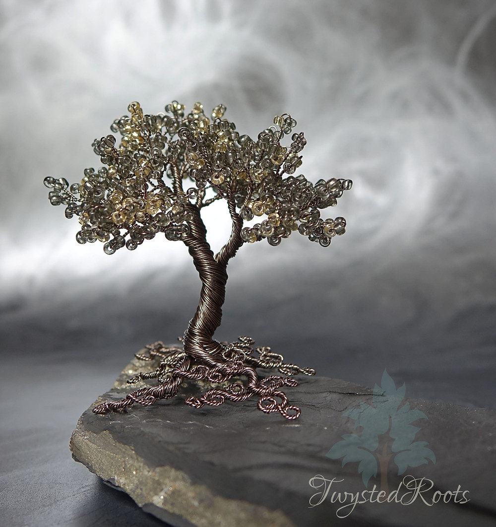 Grey and light gold bead and wire tree sculpture on a piece of Cornish shale with pyrite. Background is misty grey effect.
