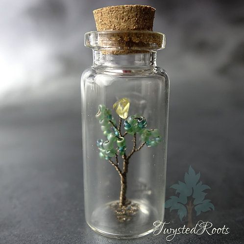 Miniature bead and wire tree seedling in a glass bottle with a cork lid