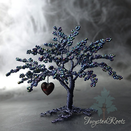 Deep blue bead and wire tree sculpture with a dark red heart hanging from a lower branch. Front view