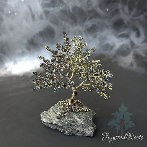 Front view of a bead and wire tree sculpture on a rock base