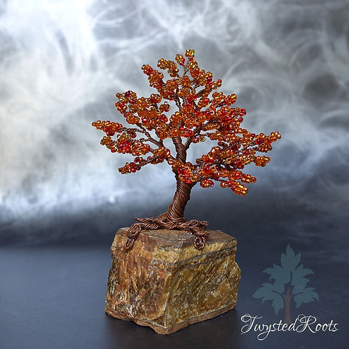 Front view red and orange bead and wire tree sculpture on a tiger eye base