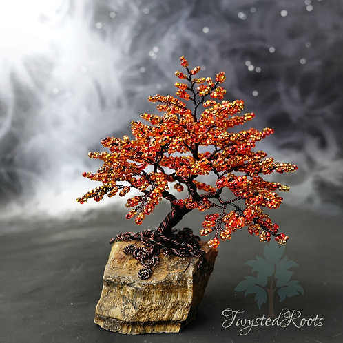 front view of an orange bead and brown/black wire tree sculpture on a tiger eye crystal base