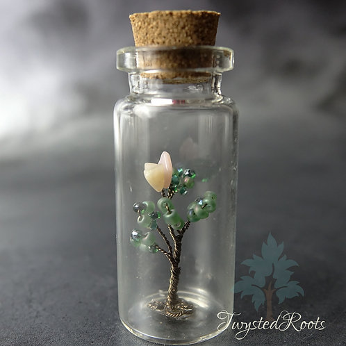 Pink opal bead and wire tree seedling in a glass bottle