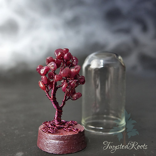 Miniature ruby wire tree on a cork base with a glass dome next to it