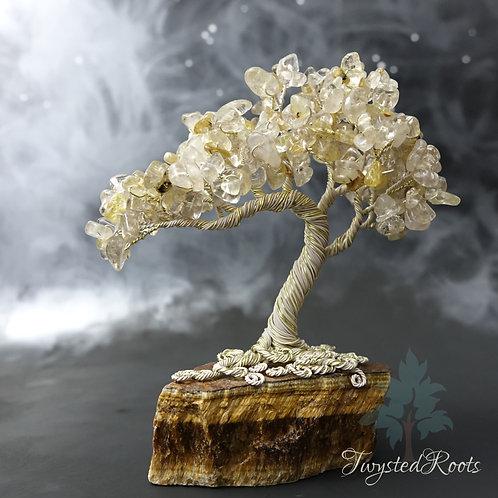 Gold rutilated quartz gemstone tree sculpture on a tiger eye base