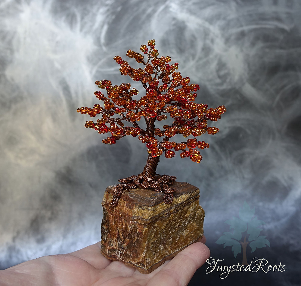 Red and orange bead and wire tree sculpture on a tiger eye crystal base by Twysted Rooots