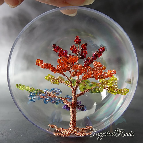 Rainbow coloured bead and copper wire tree sculpture in an acrylic bauble by Twysted Roots