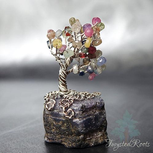 Miniature sapphire gemstone wire tree sculpture on raw sapphire