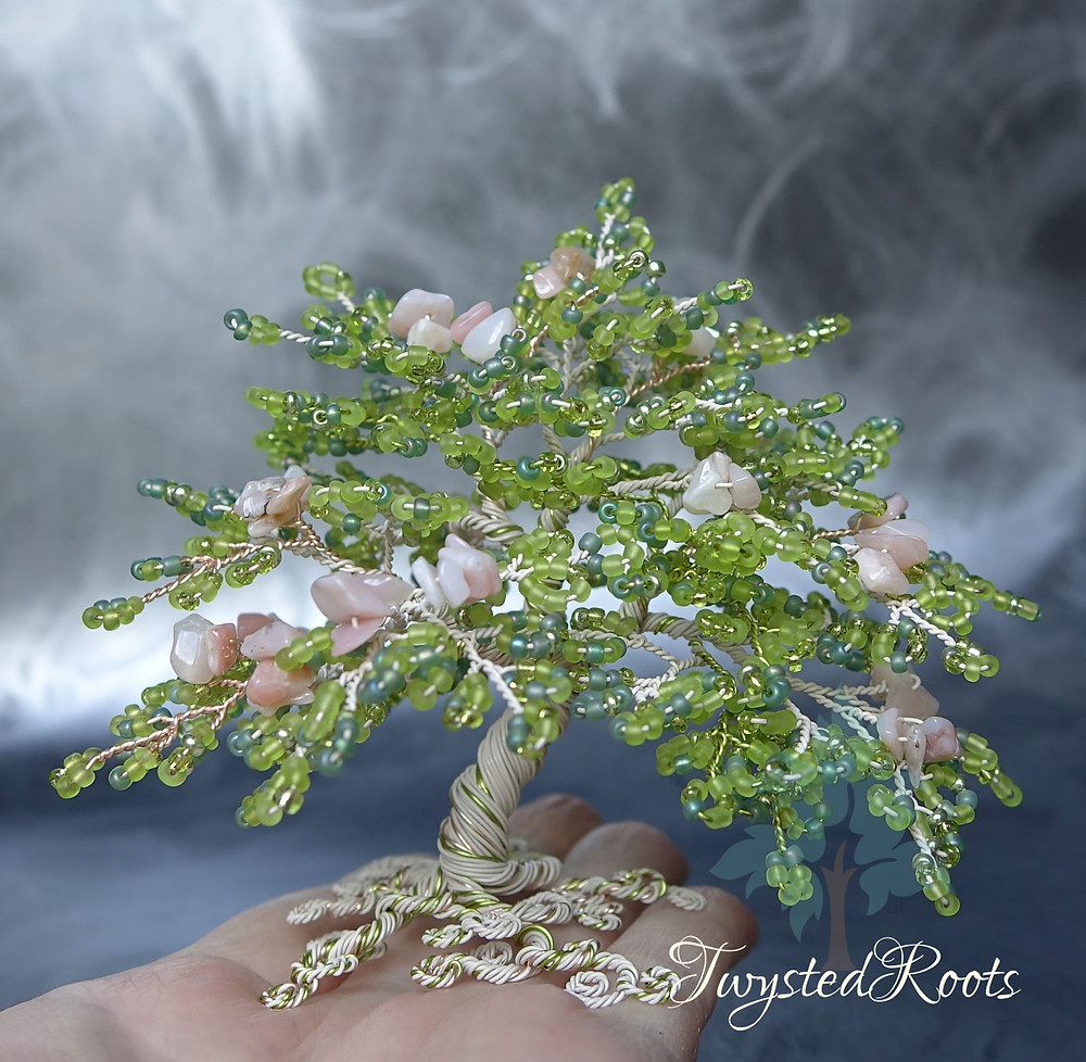 Bead and wire tree sculpture in light green and pink opal, sitting on an upturned hand
