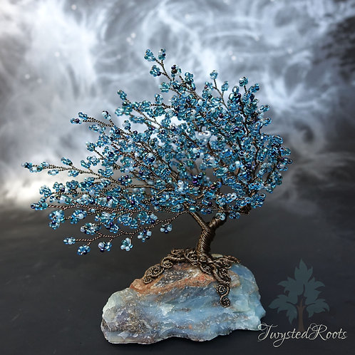 Teal blue bead and gunmetal coloured wire tree sculpture on a blue opal gemstone base
