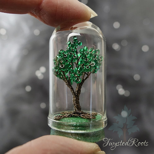 Miniature green bead and wire tree in a glass dome with a green cork base