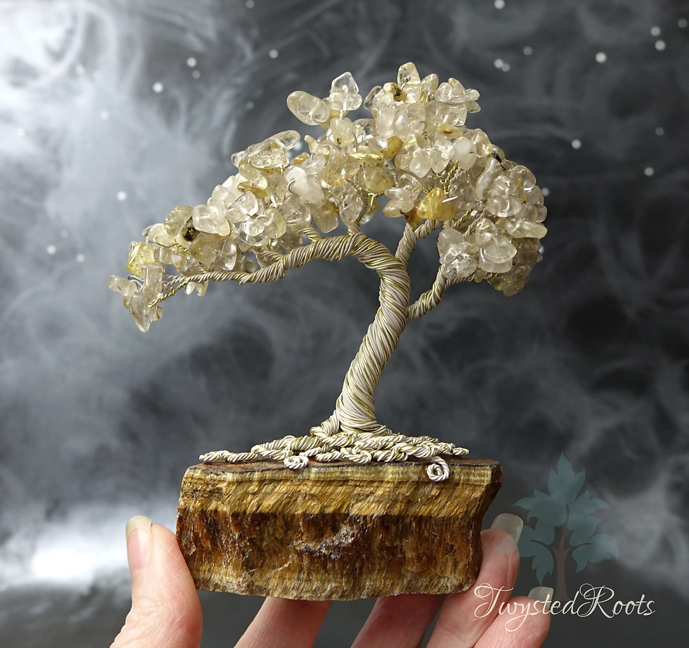 Gold rutilated quartz gemstone tree sculpture on an unpolished tiger eye crystal base, held by fingertips and thumb.