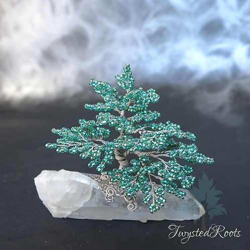 Teal and white coloured bead and wire tree on a crystal quartz base