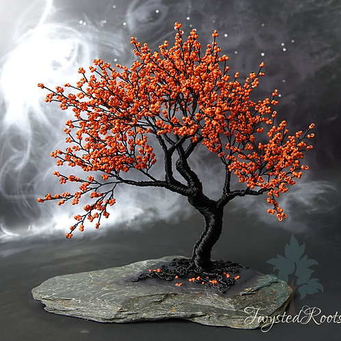Orange bead and black wire tree sculpture on a slate base
