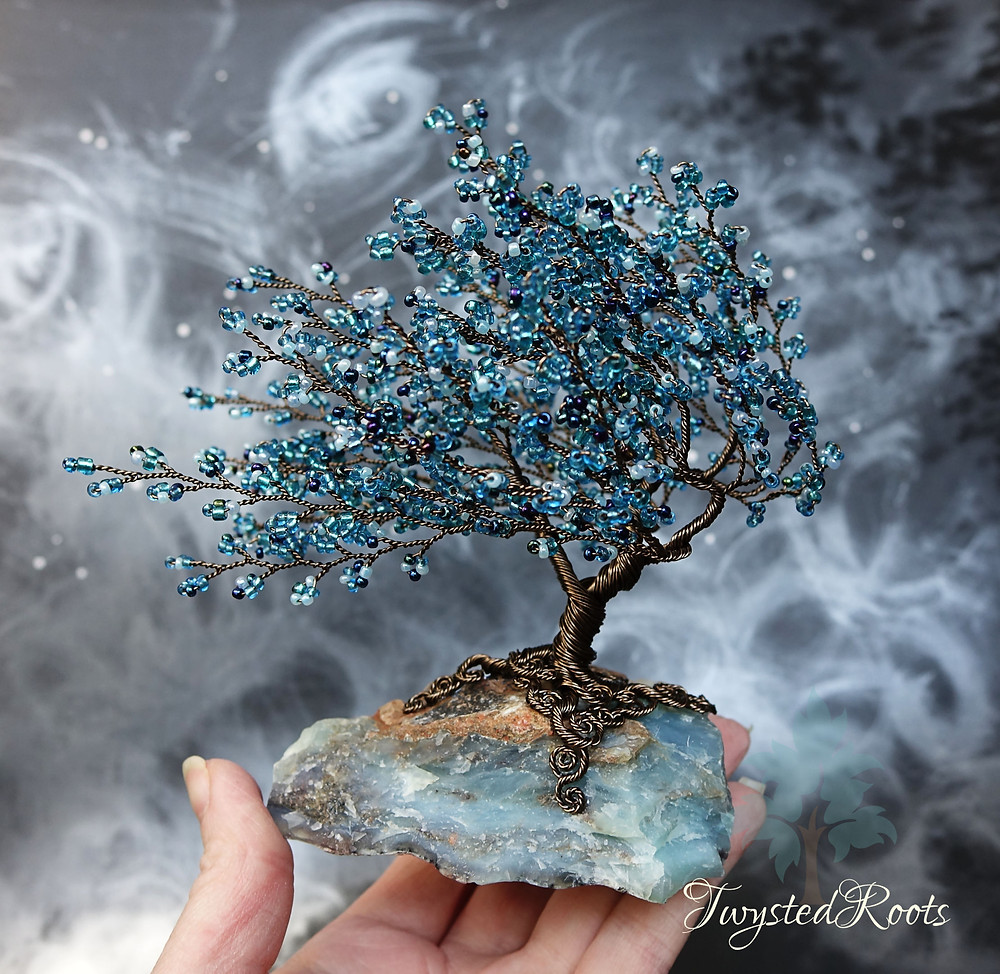 Blue bead and gunmetal coloured copper wire tree sculpture on a blue opal gemstone base, held by hand. Background is a misty grey effect. Twysted Roots logo is in the bottom right corner.