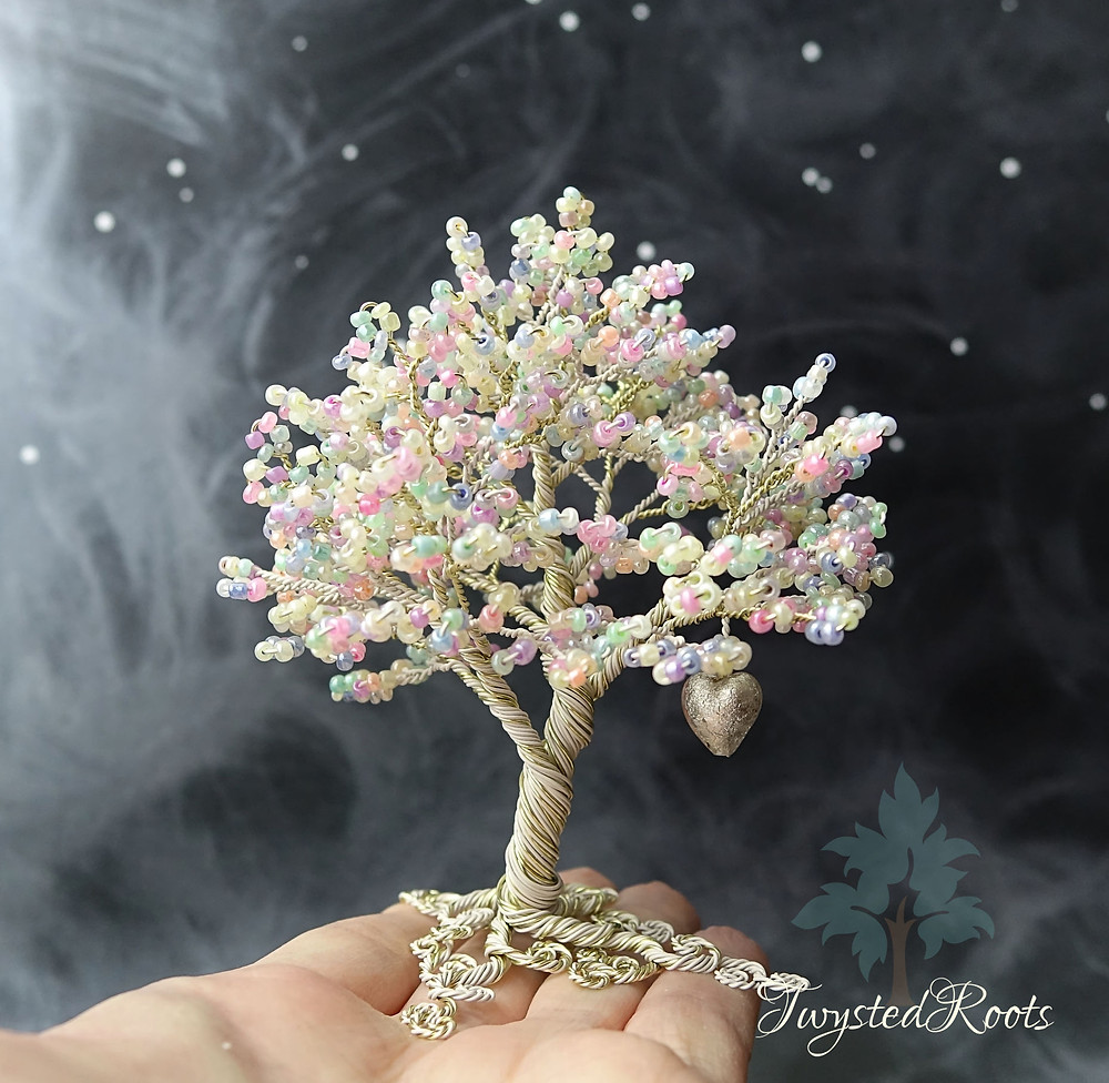 Pastel multicolours and ivory coloured bead and wire tree sculpure sitting on the fingers of an upturned hand.