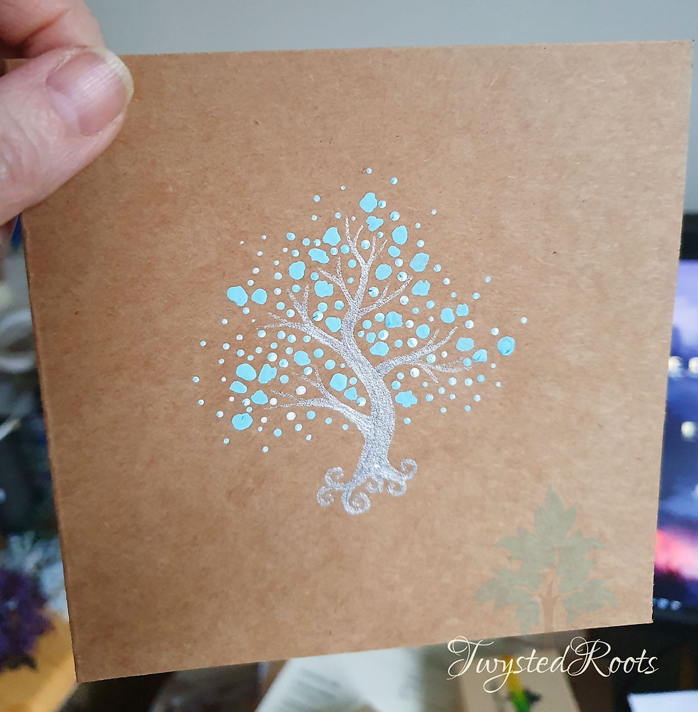 Brown card with a painting of a silver and blue tree on it by Twysted Roots
