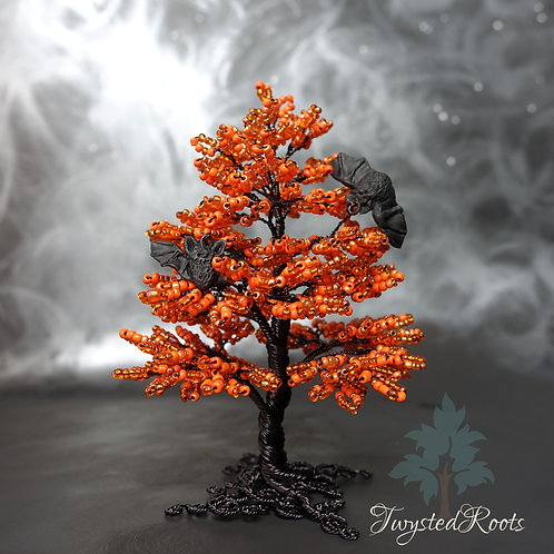 Vibrant orange and black bead and wire tree sculpture with two miniature bats within it