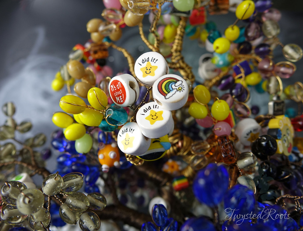 """Close up of some of the Beads of Courage on the wire tree. Some with a star and text """"I did it!"""" and others in bright different colours and shapes"""