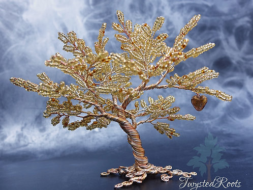 Golden yellow bead and wire tree sculpture with a golden Murano glass heart hanging from a mid right branch