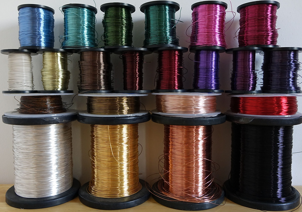 Reels of coloured copper wire in different colours, stacked on top of each other