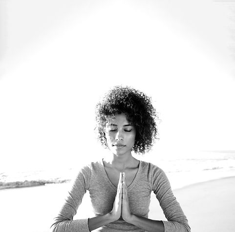 Black and white image of young attrative lady meditating on the beach