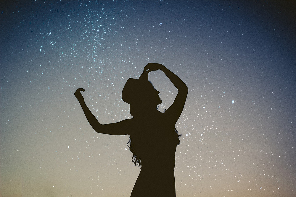 Happy woman. Woman with a hat on. Woman silhouette. Image with stars in the backdrop. Happy woman posing in the night.