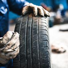 car mechanic checking tire tread