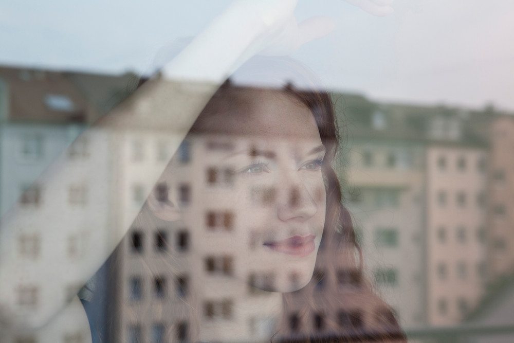 Woman staring at window and the city outside