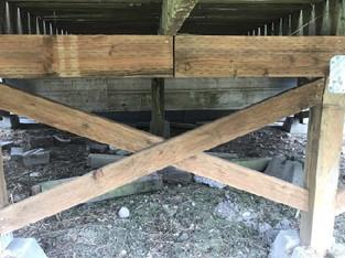 DIY deck extension. Impropeerly supported beam below a deck. Safety hazard.