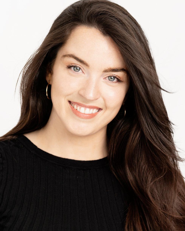 Beautiful blue eyed brunette smiling for professional headshot on white background