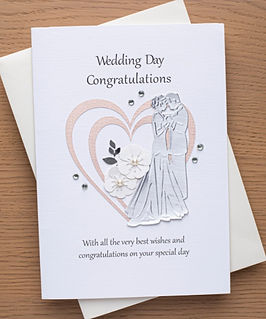 wedding day card with bride and groom and two heart shapes