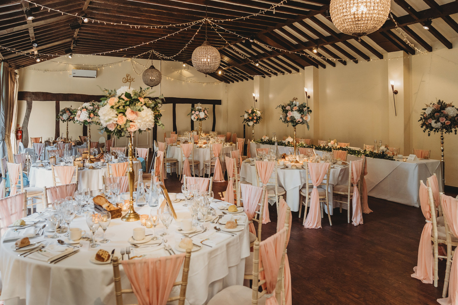 Tall gold candlestick wedding table centres at Woodhall Manor