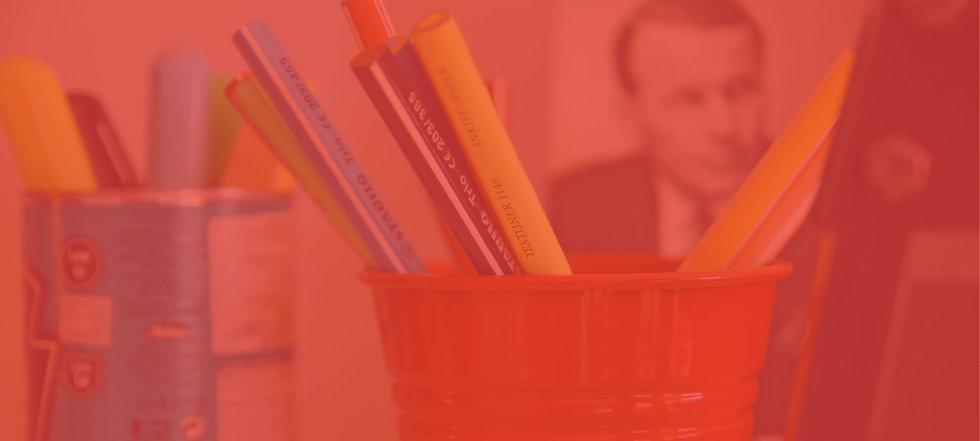 Fikirbaz'ın kalem kutusu ve arka planda kitaplar.