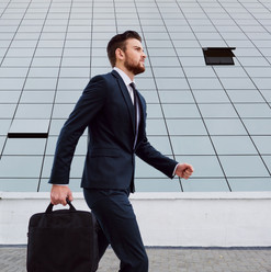 Canva - Businessman Is Walking with a Ba